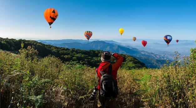 Панорамный профессиональный фотограф делает пейзажные фотографии цифровой камерой на вершине горы