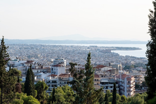 Panorama of saloniki in greece from a hill, multiple buildings and aegean sea in the distance, green trees on the foreground