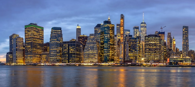 Panorama scene of new york cityscape with brooklyn bridge beside the east river at the twilight time