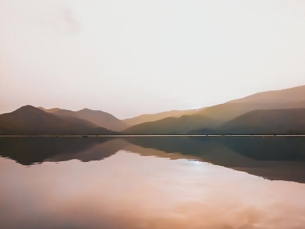 Панорама живописная красивого заката на озере с горными хребтами на фоне минимальной природы.