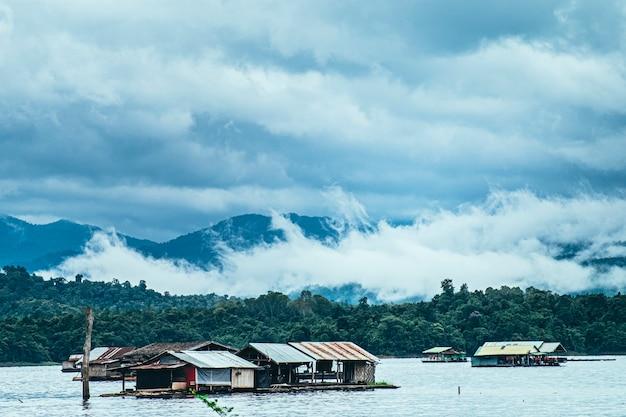 Панорама живописная рафтинг-дом с туманной горой осенью на озере в