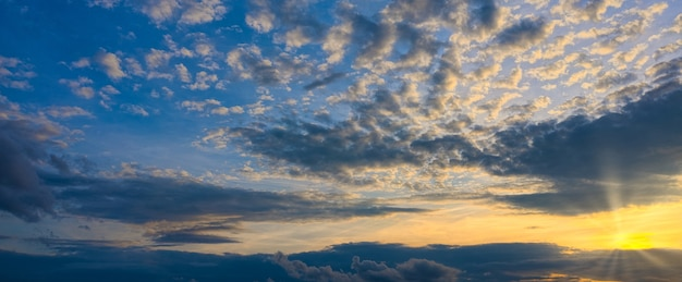 Panorama shining of the sun through the beautiful clouds of the setting sun