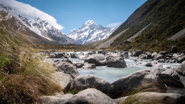 Panorama shot of glacier river leading to mountain in background made on sunny day