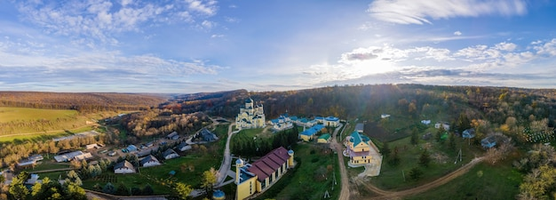 Panorama shot of the hancu monastery from the drone. churches, other buildings and green lawns. hills with bare and yellowed trees near it. moldova