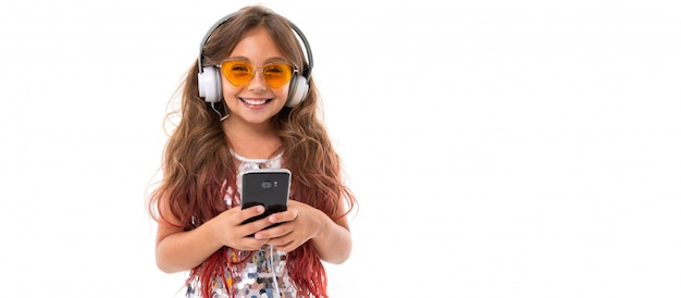 Panorama of smiling girl in glittery dress and yellow sunglasses, with white earphones listening to music and holding black smartphone isolated