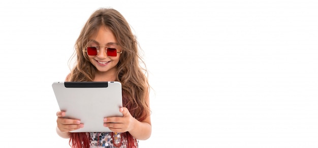 Panorama of smiling girl in square red sunglasses reading something on tablet screen isolated