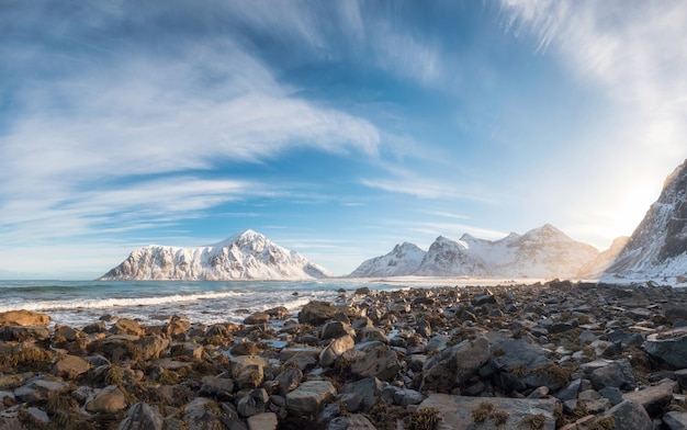 Panorama of snow mountain range with rocks in arctic ocean on winter