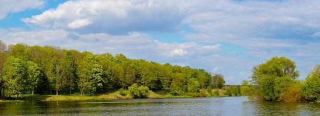 パノラマ-川岸に川と森のある春の風景。
