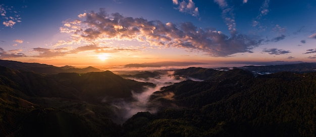 Panorama over the sunrise with blue sky background at morning time and mountain fog in the winter season