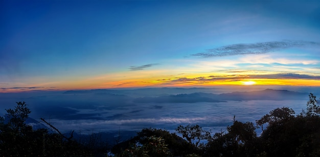 Panorama of sunrise with fog, mist and cloud cover the mountain at dawn