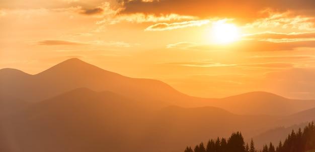 山のパノラマの夕日。山頂とオレンジ色の雲を通して輝く太陽のある風景