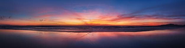 Панорама пляжа океана захода солнца города испании тарифа андалусии. атлантический океан волны фон яркий волшебный закат небо