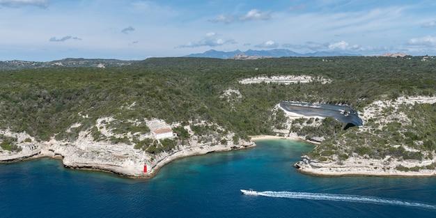 表面の山と空の中央にあるヨットの帆の上から湾と崖をパノラマで見る Premium写真
