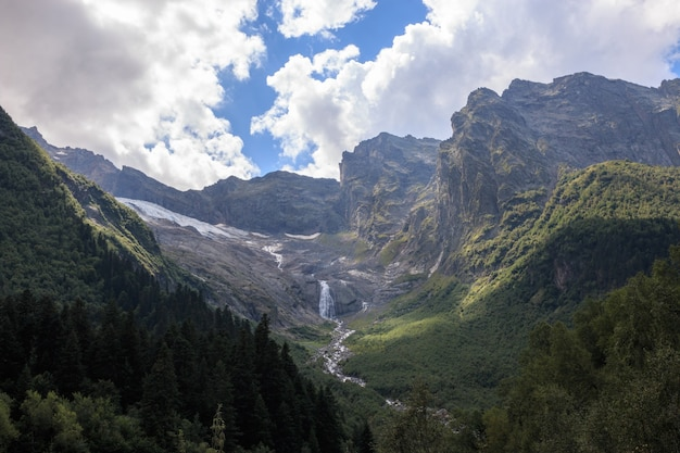 Panorama view on mountains scene and far away waterfall in national park of dombay, caucasus, russia. summer landscape, sunshine weather and sunny day