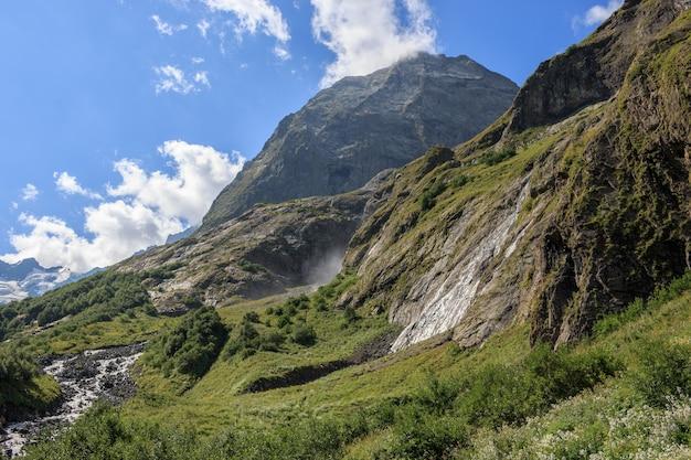 Панорама гор в национальном парке домбай, кавказ, россия. летний пейзаж, солнечная погода, драматическое голубое небо и солнечный день