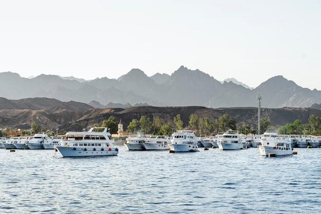 많은 흰색 전용 요트가 있는 홍해 항구의 탁 트인 전망. 산 근처 항구에 주차된 관광 선박. 풍경 이집트 샤름 엘 셰이크