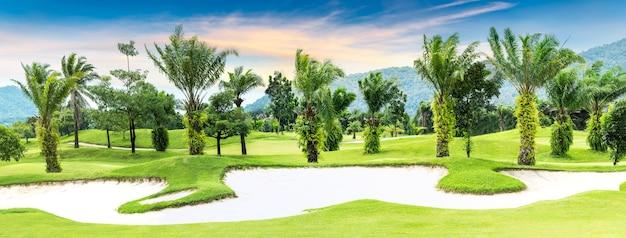 Панорамный вид на поле для гольфа с деревьями и песком