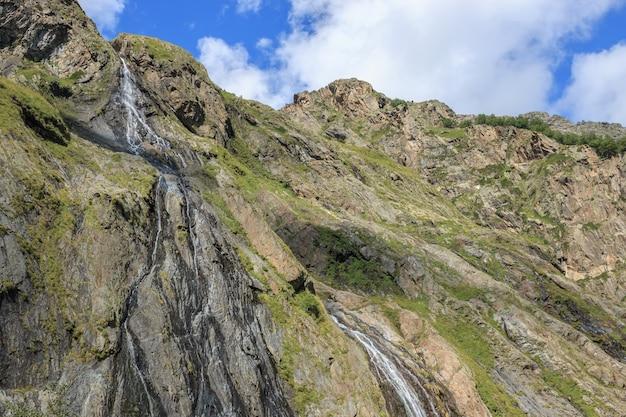 山、コーカサス、ロシアのドンベイ国立公園の滝のシーンのパノラマビュー。夏の風景、太陽の光の天気、劇的な青い空と晴れた日