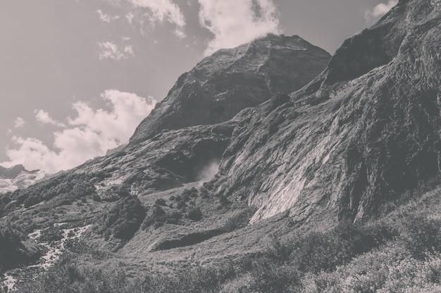 Панорамный вид сцены водопада в горах, национальный парк домбай, кавказ, россия. летний пейзаж, солнечная погода, драматическое голубое небо и солнечный день