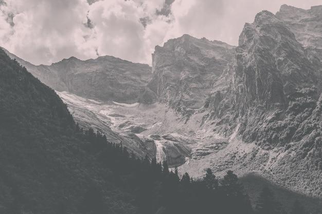 러시아 코카서스 돔베이 국립공원의 산 풍경과 멀리 떨어진 폭포의 탁 트인 전망을 감상하실 수 있습니다. 여름 풍경, 화창한 날씨와 화창한 날