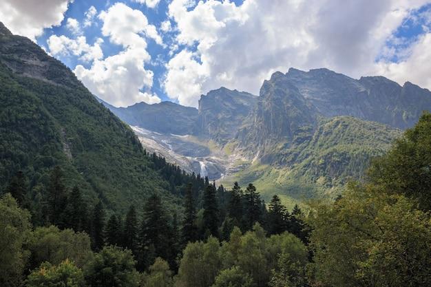 Панорамный вид на горы и далеко водопад в национальном парке домбай, кавказ, россия. летний пейзаж, солнечная погода и солнечный день
