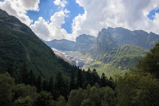 ロシア、コーカサス、ドンベイの国立公園の山のシーンと遠くの滝のパノラマビュー。夏の風景、太陽の光の天気と晴れた日