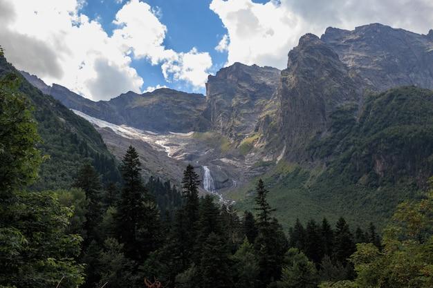 Панорамный вид на горы сцены и далеко водопад в национальном парке домбай, кавказ, россия. летний пейзаж, солнечная погода и солнечный день