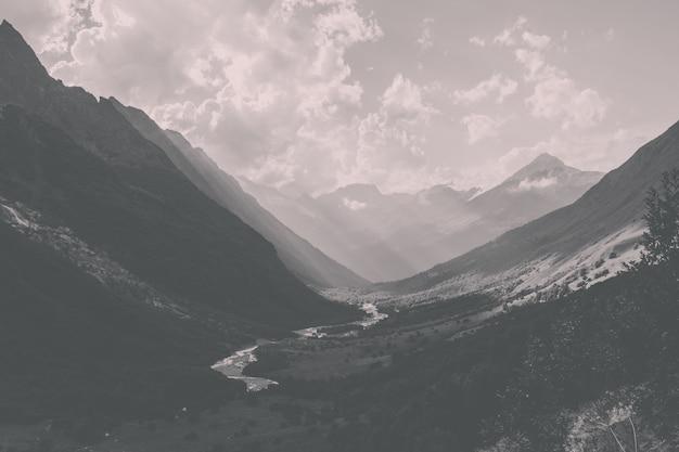 러시아 코카서스 돔베이 국립공원의 강 풍경이 있는 산의 탁 트인 전망을 감상하실 수 있습니다. 여름 풍경, 화창한 날씨와 화창한 날