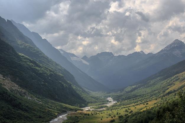 Панорамный вид на горы с речной сценой в национальном парке домбай, кавказ, россия. летний пейзаж, солнечная погода и солнечный день