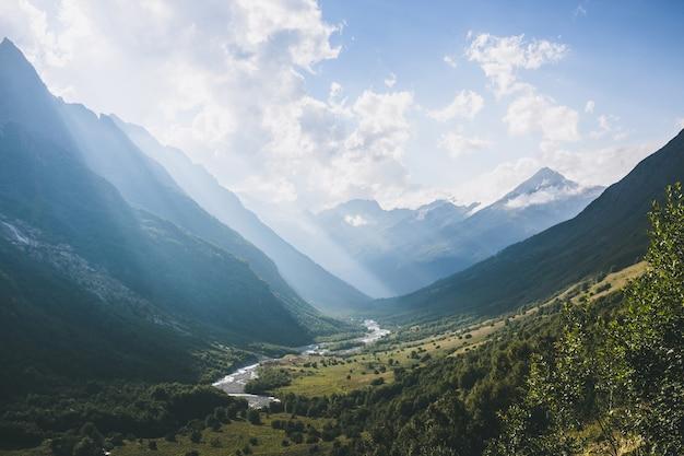 ドンベイ、コーカサス、ロシアの国立公園の川のシーンと山のパノラマビュー。夏の風景、太陽の光の天気と晴れた日
