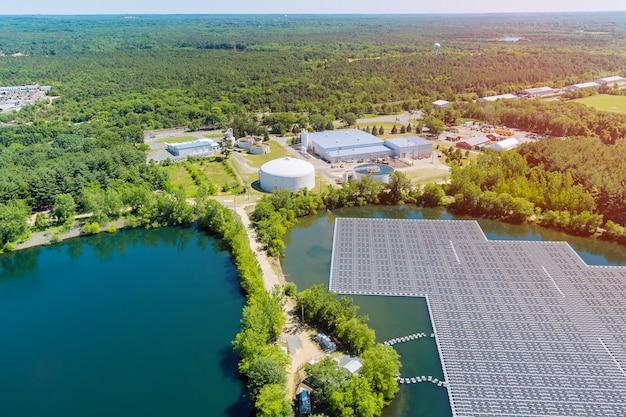 日光の下で青い池に浮かぶソーラーパネルと水に浮かぶパネルのパノラマビュー。
