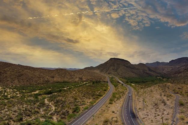 Панорамный вид на живописную дорогу в горах аризоны, красные каменные скалы и голубое небо.