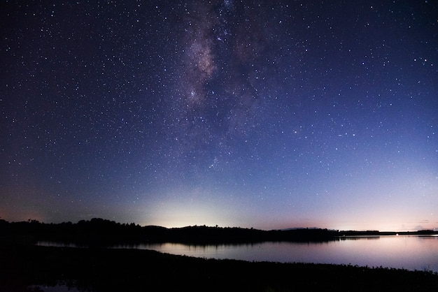 Panorama view universe space shot of milky way galaxy with stars on a night sky and lake
