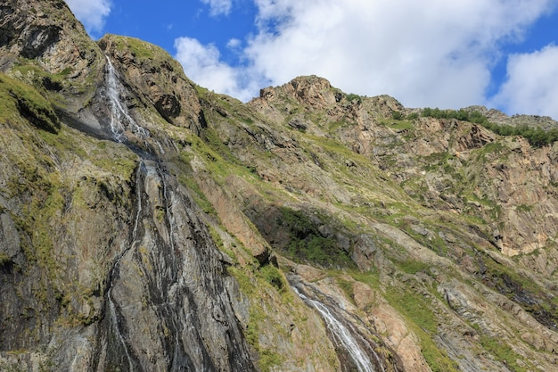 Panorama view of waterfall scene in mountains, national park of dombay, caucasus, russia. summer landscape, sunshine weather, dramatic blue sky and sunny day