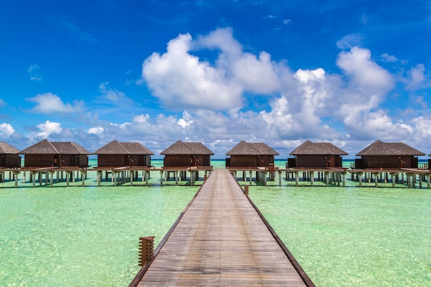 Panorama of water villas and wooden bridge in tropical beach