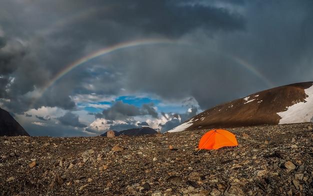 山の中に虹とオレンジ色のテントがあるパノラマ。雨と晴れの天気で虹と雪山と大気高山の風景。