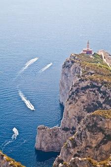 Панорама с маяком капри и лодками в солнечный день