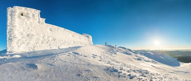 日没時の雪の中で冬の山の頂上に男とパノラマ