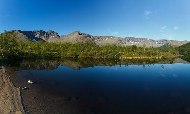 Panorama with the mountains of the khibiny, sky reflected in the lake small vudyavr. kola peninsula, russia.