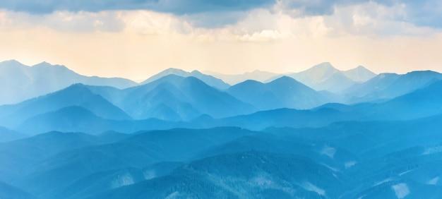 Панорама с закатом в синих горах. пейзажный вид на хребет пиков