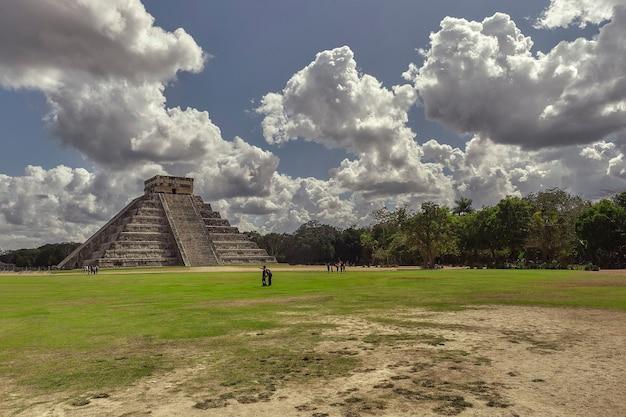 メキシコのチチェンイツァの考古学複合施設のピラミッドが、羊のような雲とそれを恍惚と賞賛する空の下の自然植生に囲まれたパノラマ。