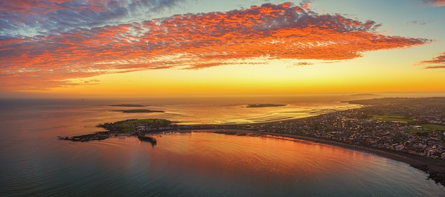 Panoramic aerial shot of land surrounded by the sea under an orange sky at sunset