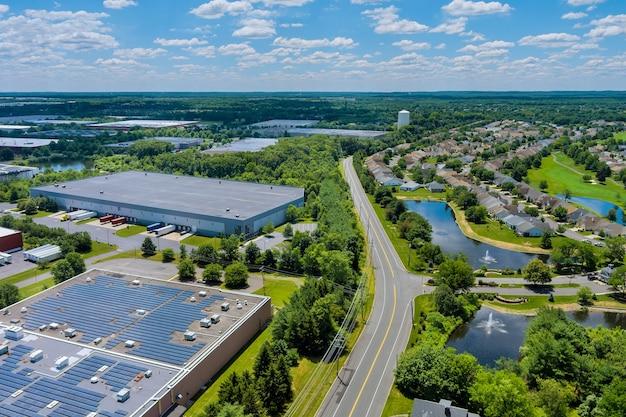 Панорамный вид с воздуха на солнечные батареи, поглощающие солнечный свет, устойчивое энергоснабжение, крыша склада