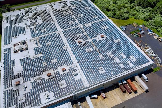 Панорамный вид с воздуха на солнечные панели на крыше завода, поглощающие солнечный свет как источник энергии