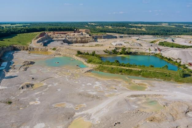鉱業活動によって形成された小さな湖がある峡谷での石の抽出に関するパノラマの空中写真