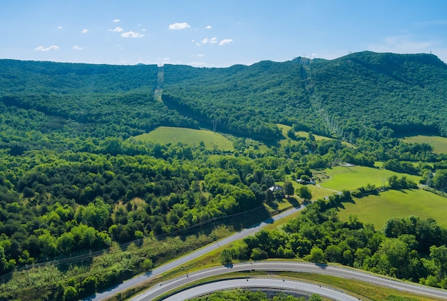 Panoramic aerial view of summer green trees forest of highway junction road in daleville town