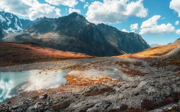 Панорамный альпийский пейзаж с красивым горным озером с ручьями в высокогорной долине с высоких гор под голубым облачным небом. солнечный горный пейзаж с зеркальным ледниковым озером в высоких горах.