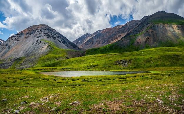 曇り空の下の大きな山から高原の緑の谷の小川と美しい浅い山の湖とパノラマの高山の風景。ミラー氷河湖と雨の山の風景。