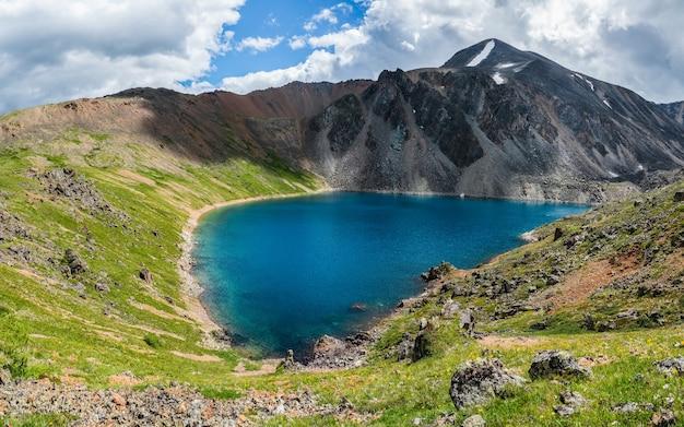 Панорамный альпийский пейзаж с горным озером в зеленой долине и ледником под пасмурным небом. атмосферный горный пейзаж с красивым ледниковым озером среди залитых солнцем холмов и скал на фоне горного хребта.