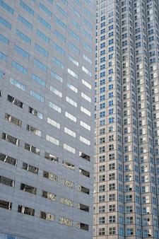 Панорамный и перспективный широкий угол обзора на стальной синий фон стеклянных высотных зданий небоскребов в современном футуристическом центре города ночью бизнес-концепция успешной промышленной архитектуры